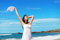 Happy woman on beach travel and vacation joyful in white dress enjoying dancing the during summer walk relax playa de verdicio Stock Photos