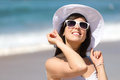 Happy woman on beach vacation smiling and enjoying summer beautiful caucasian girl in holidays wearing white sunglasses and hat Royalty Free Stock Photos