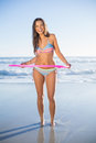 Happy woman in bikini playing with hula hoop on the beach on a sunny day Stock Photos