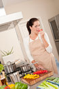Happy woman biting red pepper in the kitchen Royalty Free Stock Photo