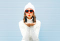 Happy woman blowing red lips sends air kiss wearing a heart shape sunglasses, knitted hat, sweater over blue Royalty Free Stock Photo