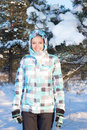 Happy woman in blue sporty checkered jacket walking in winter fo young forest Stock Image