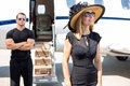 Happy woman with bodyguard and private jet in women wearing sunhat sunglasses background Stock Photography