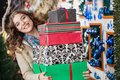 Happy woman carrying stacked gift boxes in store portrait of young christmas Stock Images