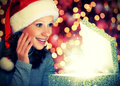 Happy woman in a christmas cap opens the magic box gift Stock Photo