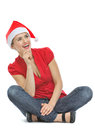 Happy woman with Christmas hat sitting on floor Royalty Free Stock Images