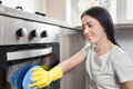 Happy woman cleaning oven