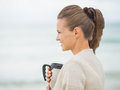 Happy woman on cold beach with cup of beverage young hot Royalty Free Stock Photo