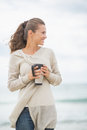 Happy woman on cold beach with cup of hot beverage young Royalty Free Stock Image