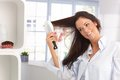 Happy woman combing hair young long by hairbrush smiling Stock Photography