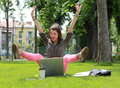 Happy woman with computer in an urban park excited a laptop raising her hands and legs up Royalty Free Stock Image