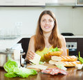 Happy woman cooking sandwiches with vegetables and cheese Royalty Free Stock Images