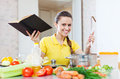 Happy woman cooking vegetables with book at domestic kitchen Royalty Free Stock Images