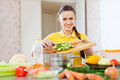 Happy woman cooking vegetables at domestic kitchen Royalty Free Stock Images