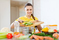 Happy woman cooking vegetables at kitchen Royalty Free Stock Photography