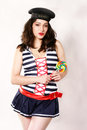 Happy woman in costume smiling dressed pinup sailor with a large lollipop her hand Royalty Free Stock Photos