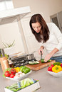 Happy woman cutting zucchini in the kitchen Royalty Free Stock Photo