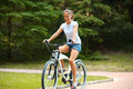 Happy Woman is Cycling in Summer Park Royalty Free Stock Photo
