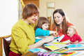 Happy woman with daughter and children playing at home