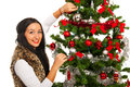 Happy woman decorate christmas tree and smiling to camera Royalty Free Stock Photography