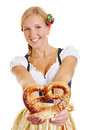 Happy woman in dirndl offering smiling a a pretzel Stock Images