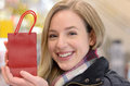 Happy woman displaying a small Christmas gift Royalty Free Stock Photo