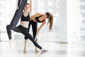 Happy woman doing aerial yoga with trainer in studio Royalty Free Stock Photo
