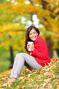 Happy woman drinking coffee in fall forest outdoor city park girl sitting relaxing enjoying hot drink or tea disposable Royalty Free Stock Photography