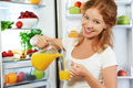 Happy woman drinking orange juice about refrigerator Royalty Free Stock Photo