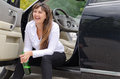 Happy woman drunkard in a car sitting on the sill of the open drivers door clasping her bottle of spirits and laughing Stock Photo