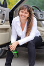 Happy woman drunkard in a car sitting on the sill of the open drivers door clasping her bottle of spirits and laughing Royalty Free Stock Images