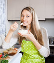 Happy woman eating cottage cheese in home kitchen Royalty Free Stock Photography