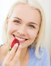 Happy woman eating strawberry at home Royalty Free Stock Photo