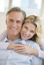 Happy woman embracing man from behind at home portrait of mature women men Stock Photography