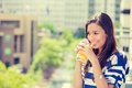 Happy woman enjoying sunny day on balcony of her apartment closeup portrait beautiful off a drinking orange juice a urban city Stock Photography