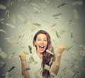 Happy woman exults pumping fists ecstatic celebrates success under a money rain portrait falling down dollar bills banknotes Stock Photography