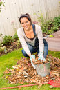 Happy woman filling bucket leaves fall gardening housework rake Stock Images