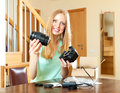 Happy woman fixing objective onto new digital camera at home in living room Royalty Free Stock Photos