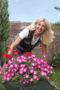 Happy woman with flowers in her garden Royalty Free Stock Photo