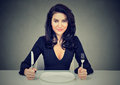 Happy woman with fork and knife sitting at table with empty plate Royalty Free Stock Photo