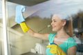 Happy woman in gloves cleaning window with rag people housework and housekeeping concept and cleanser spray at home Royalty Free Stock Image