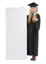 Happy woman in graduation gown showing billboard young blank and thumbs up Royalty Free Stock Photos
