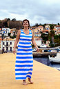 Happy woman in greek flag dress beautiful brunette wearing color on the waterfront of the small town greece Royalty Free Stock Image