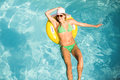 Happy woman in green bikini floating on inflatable tube in swimming pool Royalty Free Stock Photo