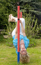 Happy woman hanging on horizontal bar young the high in the garden Stock Image
