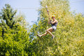 Happy woman hanging on zip line in forest full length of young against trees Stock Photos
