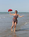 Happy woman with hat dancing at sea red Royalty Free Stock Image