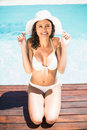 Happy woman in hat sitting by pool side Royalty Free Stock Photo