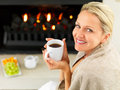 Happy woman having coffee by the fireplace Royalty Free Stock Photos