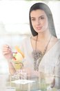 Happy woman having ice cream cup at cafe table smiling picture through window Royalty Free Stock Photo